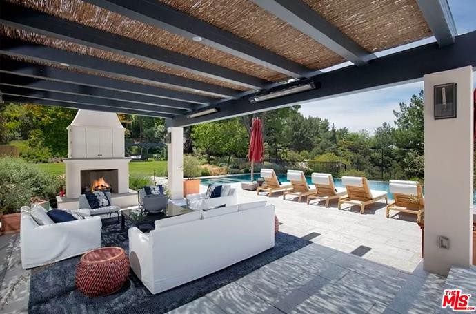 """The outdoor entertainment area, fitted with a pizza oven, fireplace and lounges. <br><br> *Image by [MLS/Zillow](https://www.zillow.com/homedetails/8-Beverly-Park-Beverly-Hills-CA-90210/20533668_zpid/?