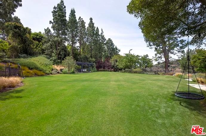 """The spacious garden that includes a swinging chair hanging from a tree. <br><br> *Image by [MLS/Zillow](https://www.zillow.com/homedetails/8-Beverly-Park-Beverly-Hills-CA-90210/20533668_zpid/?
