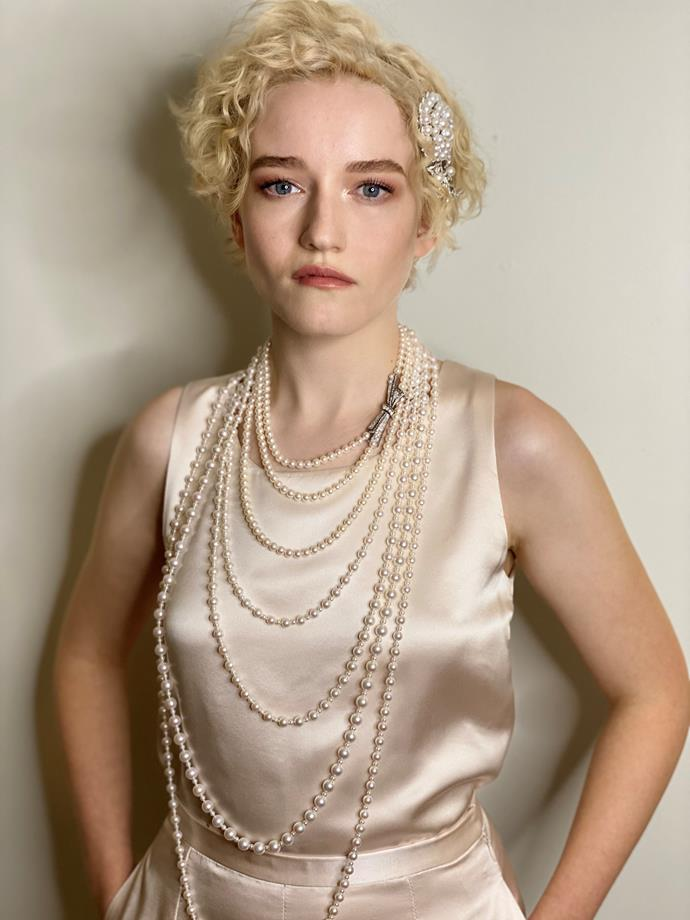 Julia Garner wearing a powder pink satin sleeveless blouse and pants and jewellery by Chanel.