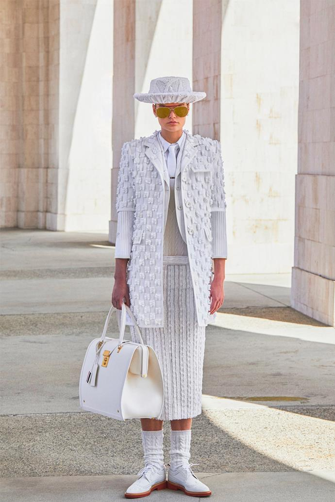 """**Thom Browne** <br><br> This androgynous collection is based on """"the first lunar games...in a coliseum on the moon,"""" according to the designer himself. With the entire collection in shades of cream and white, the tailored yet sporty looks range from pleated skirts, vests, cropped trousers, and top coats."""