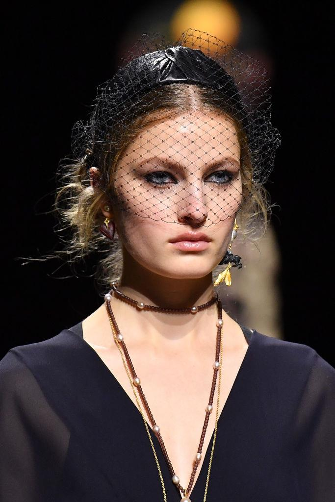 **Dior** <br><br> A distinct departure from their last show's neutral beauty look, this season Dior went all out on the eyes with a thick, clean kohl eyeliner look. <br><br> Hair was kept in a messy, undone up-do with knotted headbands that got all of our attention.