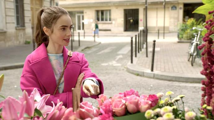 **3. Emily's Pink Coat And Roses Moment**<br><br>  Of all of Emily's outfits throughout the series, this moment arguably merged Field's penchant for 'fabulous' with what a real-life Emily would actually wear in Paris. The bright pink cashmere Kenzo coat and Chanel handbag brought the dream factor, while the pastel tee, black tights and runners (not seen here) rounded out the look with a pleasant touch of realism.<br><br>  *Le mood:* *La vie en rose*, of course.