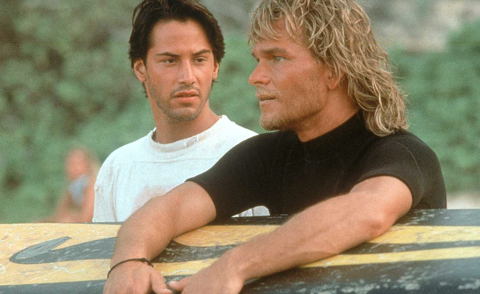 ***Point Break* (1991)** <br><br> FBI agent Johnny Utah (Keanu Reeves) goes undercover to infiltrate a group of surfers suspected of being behind a series of bank robberies. However, things get complicated when he get's a little too close to the group, particularly their leader, Bodhi (Patrick Swayze)