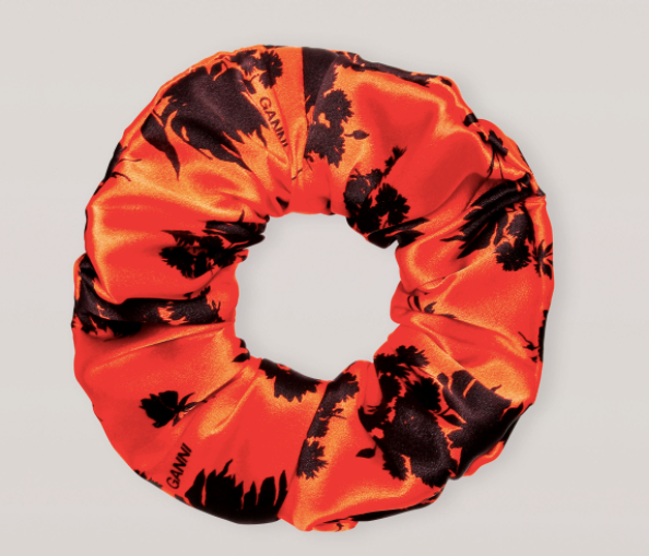 """Silk Stretch Scrunchie, $35 by [GANNI](https://www.ganni.com/en-au/silk-stretch-satin-scrunchie-A3071.html?dwvar_A3071_color=Flame&dwvar_A3071_size=One%20size&quantity=1
