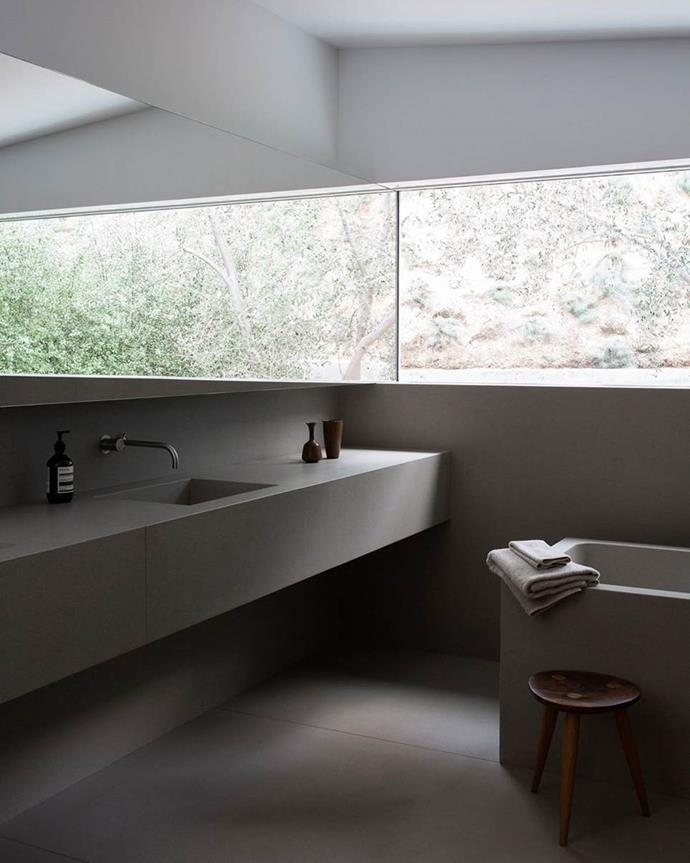 """The long window in the minimalist bathroom makes the outdoor shrubbery the focal point, similar to Kim Kardashian and Kanye West's Axel Vervoordt-designed [house](https://www.elle.com.au/culture/kardashian-jenner-houses-24316 target=""""_blank"""") in Calabasas. Plus, no aesthetically-pleasing bathroom is complete without Aesop products."""