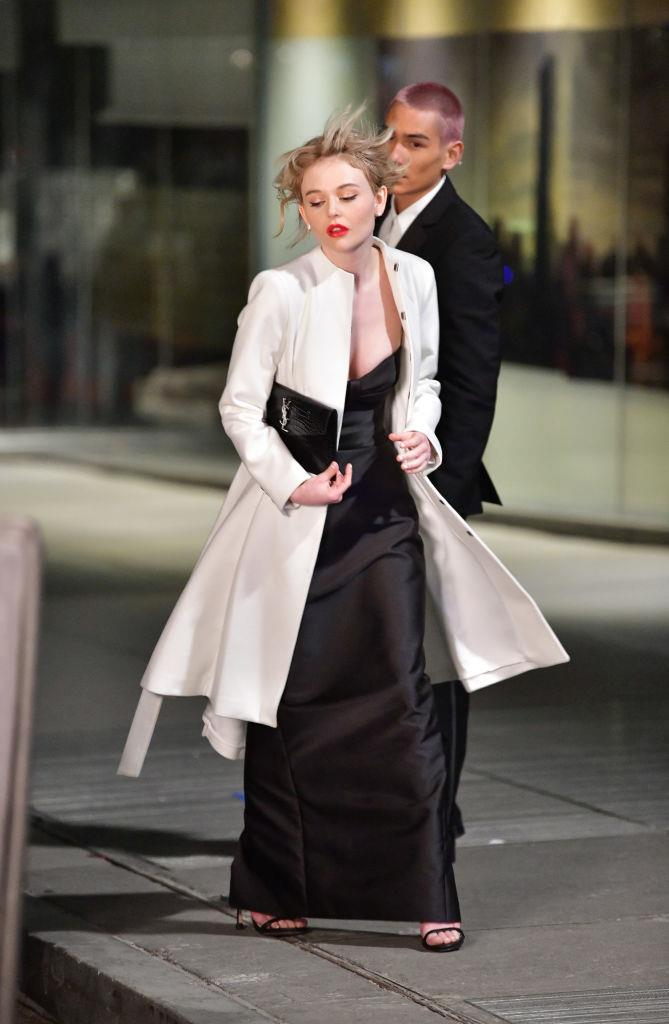 """**Evening Wear**<br><br>  It wouldn't be *Gossip Girl* without some gala-worthy gowns, no? That said, we weren't expecting something as simple as a slip dress to make the cut (albeit with a Saint Laurent bag). Emily Alyn Lind (pictured here, alongside Mock), plays Audrey, who """"has been in a long term relationship and is beginning to wonder what more could be out there"""". Intrigued."""