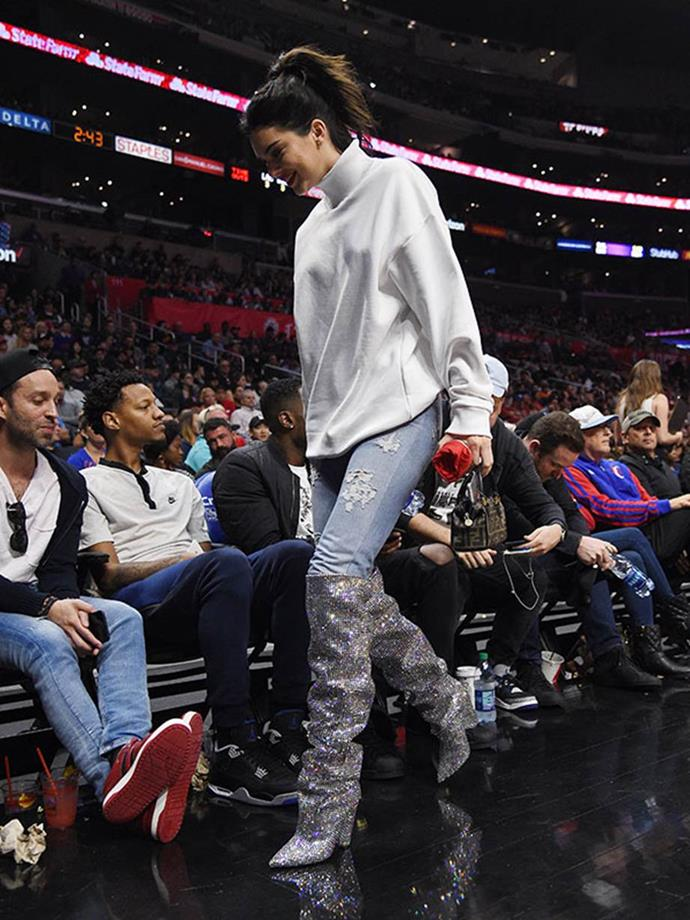 Kendall Jenner wearing $10,000 Saint Laurent glitter boots to a Los Angeles Clippers game.
