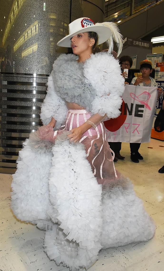 Lady Gaga arriving at a Japanese airport in a full-length ruffled ball gown and a wide-brimmed hat.