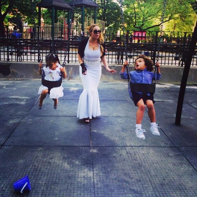 Mariah Carey at the playground with her children in a white halter-neck gown and a black bolero.