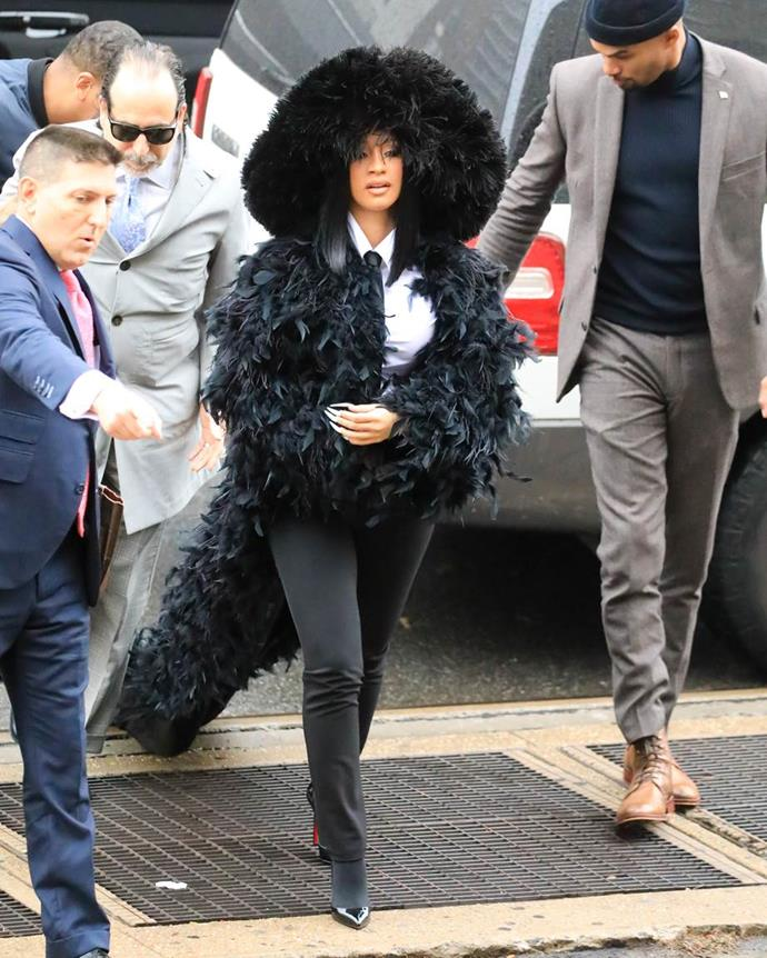 Cardi B wearing a feather jacket with a floor-length train and fur hat to appear in court.
