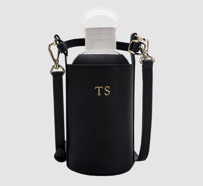 """Customisable Drink Bottle in Leather Holder with Strap, $99.95 by [The Daily Edited](https://www.thedailyedited.com/black-reusable-drink-bottle