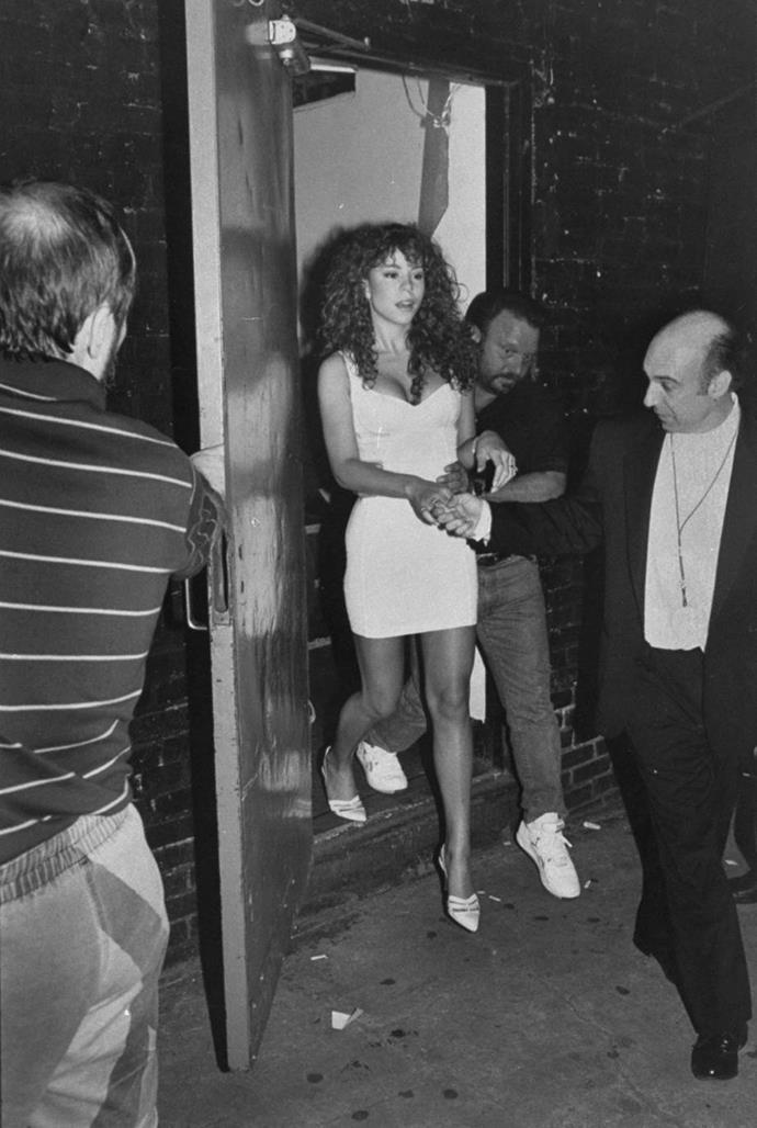 Mariah Carey being escorted out of a party in 1991.