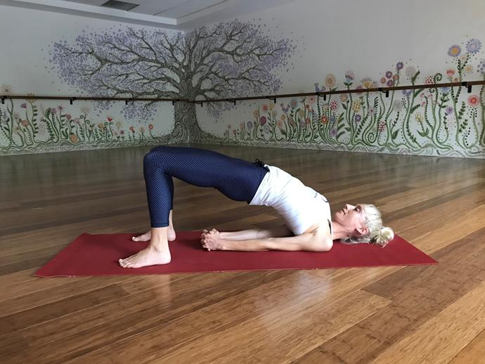 """**Bridge Pose**<br><br>  If your mind is buzzing and it's giving your gut grief, bridge pose is an ideal place to start your stress-relieving sequence.<br><br>  """"Bridge pose is great for calming the mind and aiding digestion,"""" Kendall explains.<br><br>  *How to:*<br><br>  1. Lie on back and take feet to hip distance and parallel under sit bones.<br>  2. Place hands by side on floor.<br> 3. As you inhale lift the hips slowly and as you exhale wriggle the shoulders under the body to interlace the hands.<br>  4. Stay five to 10 slow, mindful breaths.<br><br>   *Note: To make this more restorative, place a yoga block) under hips and stay for five minutes.*"""
