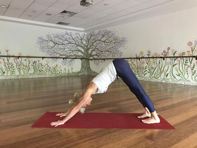 """**Downward Facing Dog**<br><br>  After a day of working at your desk (or dining table) and building up feelings of tension, your spine and posterior chain in general may need a little extra love.<br><br>  """"Downward facing dog is ideal for relieving stress in spine, lengthening the hamstrings and calves and aiding digestion,"""" says Kendall.<br><br>  """"It's energising—in just the right ways—to keep you moving at a steady, sustainable pace.""""<br><br>   *How to:*<br><br>  1. From all fours, take your hands out in front of the shoulders a little.<br>  2. Curl your toes under and lift the knees until you can ease your sit bones up and back.<br>  4. Soften or bend the knees in order to lengthen the spine and wrap your under arms in towards each other as if 'checking each other out'.<br>  5. Let the head drop and enjoy 10 steady breaths."""