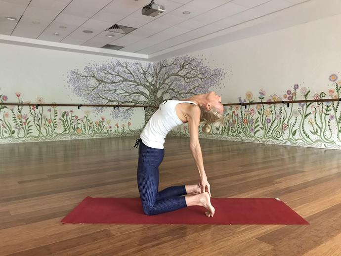 """**Camel Pose**<br><br>  Following on from downward dog, camel pose is great for enabling a calm yet positive shift in the body.<br><br>  """"It gives you a healthy burst of uplifting energy,"""" Kendall says.<br><br>  *How to:*<br><br>  1. Start by kneeling in your knees, and then curl your toes under.<br> 2. Place your hands behind you on sacrum with fingertips pointing down towards sit bones. <br> 3. Ease the tailbone under, press the hips gently forward and climb your rib cage up the spine and back to ease into the pose. Stay there or take hands to heels and gently drop your head back.<br>  4. Stay as long as feels good. Engage core to come out."""
