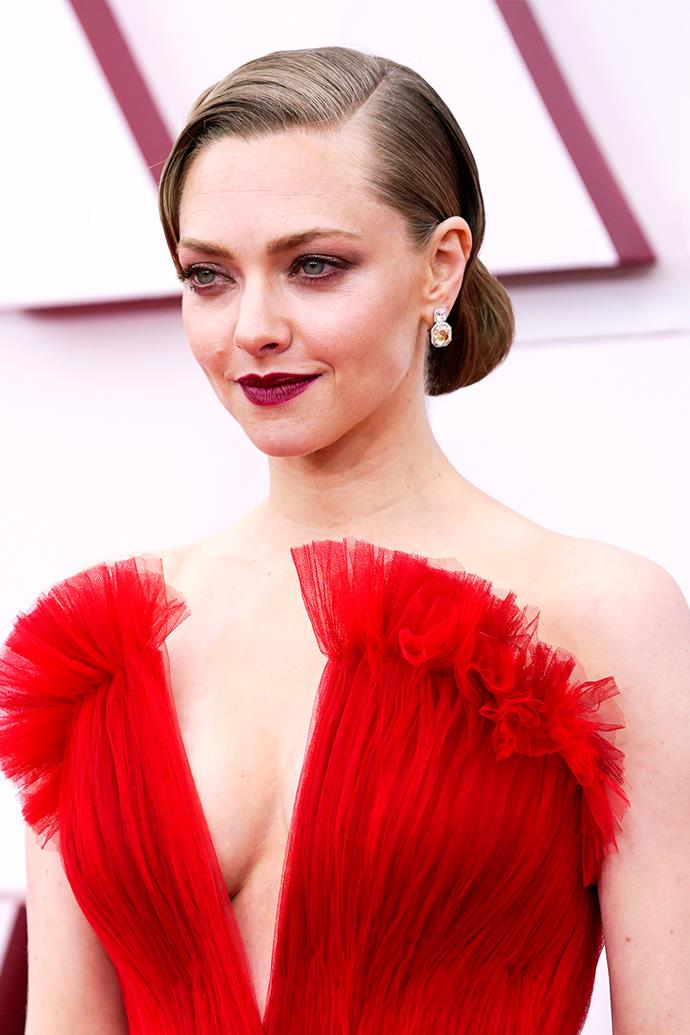 Amanda Seyfried sported a slicked back updo with a side part, a deep rose eye and a bold scarlet lip.