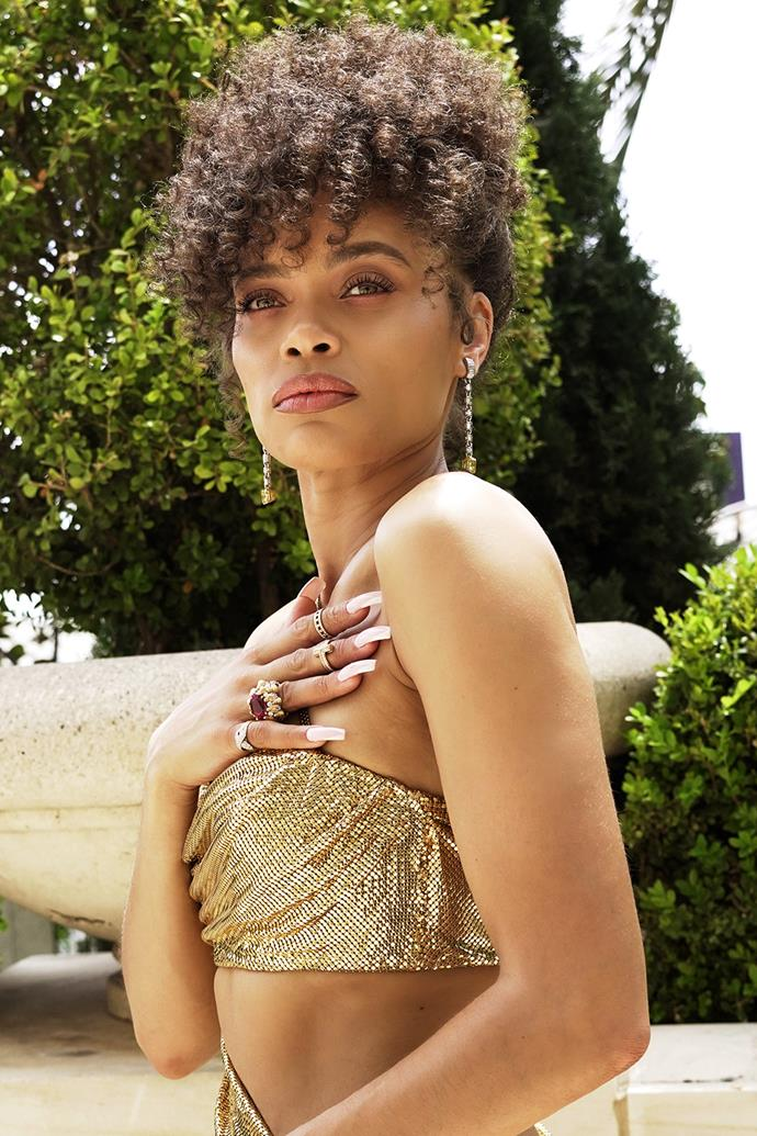 Andra Day stunned pinning her natural curls into an updo with a side fringe, as well as a caramel eye and neutral lip.