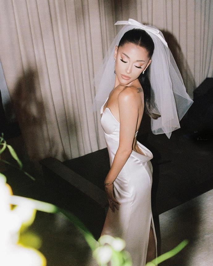 **Ariana Grande in Vera Wang (2021)**<br><br> Ariana Grande promised Vera Wang that when the time came for her to get married, she would choose the famed designer to make her dress. Earlier this year, she kept her promise. <br><br> For her big day, Ari wore a custom lily-white silk charmeuse strapless empire waist column gown, accented with a sculpted neckline, per Vogue U.S.. The dramatic plunging back was complimented by a satin bow, and she matched it with a lily-white, tulle shoulder length hand pleated bubble veil. Her shoes were custom Giuseppe Zanotti platform heels.