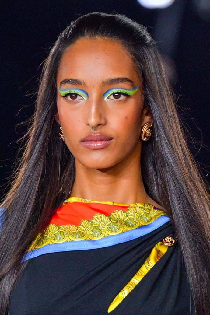 **Sixties Specs** <br><br> Bursts of colour were swept across each model's face as they took to the Versace spring/summer 2022 runway. From tricolour moments of royal blues, limes and icy silvers to solid emeralds across the entire lid, the hues remained bold and striking, paired perfectly with a natural complexion, slight flush to the cheeks and a glossy lip. <br><br> *Image: Versace spring/summer 2022.*