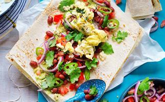 Scrambled eggs, smashed avocado and bean breakfast wrap