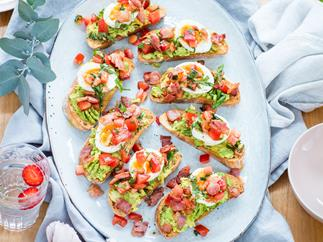 Brunch bruschetta with bacons, eggs and smashed avocado