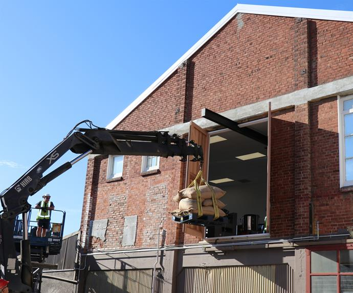 The first batch of beans delivered by a crane into the new OCHO chocolate factory.