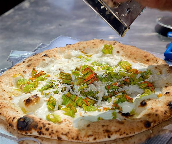 Conciato Romano is grated on a white pizza with zucchini flowers at Ciro Salvo
