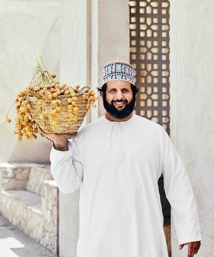 A Nizwa date merchant with a basket of Hilali dates