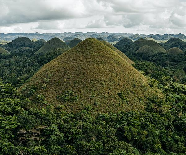 "**BOHOL, THE PHILIPPINES**<br> ""The Chocolate Hills of Bohol are hidden from view. From the city of Tagbilaran on the southern island of Bohol, it's a two-hour drive deep into the jungle to find them.<br><br> ""Once you arrive at a lookout in a town named Carmen, these very strange cone-shaped hills stretch for miles in every direction. There are more than 1,000 of them; some say nearly 1,800. They're covered in grass that turns brown in the dry season, which is what gives them their name. It's thought they were formed by the uplift of coral deposits long ago and the action of rainwater and erosion.<br><br> ""This particular afternoon was humid and the late afternoon light mixed with smoke haze from fires in the villages below was beautiful.""<br><br> *Adam Gibson, [adamgibson.com.au](https://adamgibson.com.au/