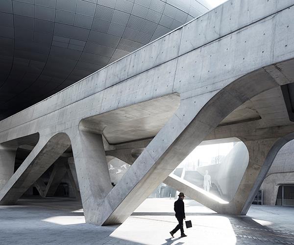 "**SEOUL, SOUTH KOREA**<br> ""On my first trip to Seoul in the winter of 2016, during half a day off work, I set out to explore the old city and the DDP, aka the Dongdaemun Design Plaza, the city's cultural hub.<br><br> ""Designed by Zaha Hadid and opened in 2014, the DDP has a façade of shapely aluminum panels and spans 38,000 square metres of exhibition spaces and museums covering the arts, design and technology, and landscaped parks used by seemingly everyone in this crowded megacity.<br><br> ""The light was beautifully soft on this chilly morning and all was quiet. The few people who were out and about moved through my shot in monotones, the same palette as the monumental concrete structures around them.""<br><br> *Sharyn Cairns, [sharyncairns.com.au](https://www.sharyncairns.com.au/