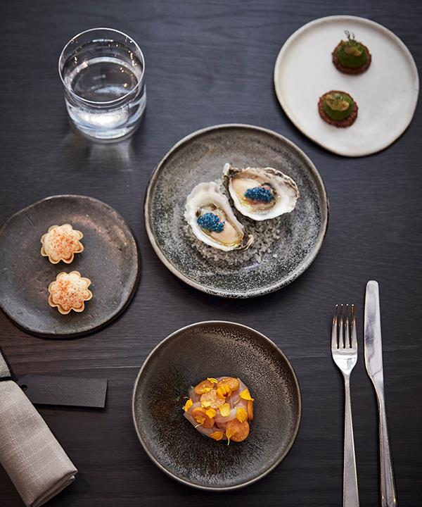 (Clockwise from top left): Parmesan tart with tomatillo, oyster with finger lime and scampi roe, cucamelon with pistachio butter, and kingfish with Cape gooseberries (photography: Will Horner).