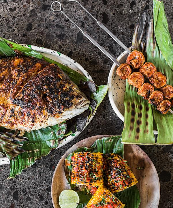 Clockwise from left: barramundi fillet in banana leaf, paprika and garlic prawn skewers, barbequed corn.