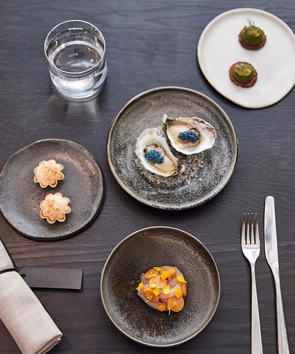 Clockwise from left: Parmesan tart with tomatillo, oyster with finger lime and scampi roe, cucamelon with pistachio butter, and kingfish with Cape gooseberries.