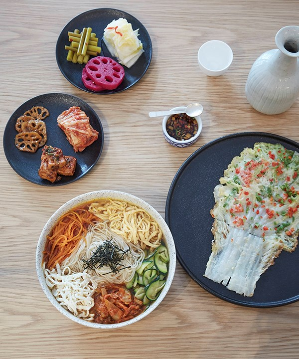 Janchi guksu - noodles, egg and vegetables (left) and baechu jeok made with Napa cabbage, (right) with seasonal sides and pickles.