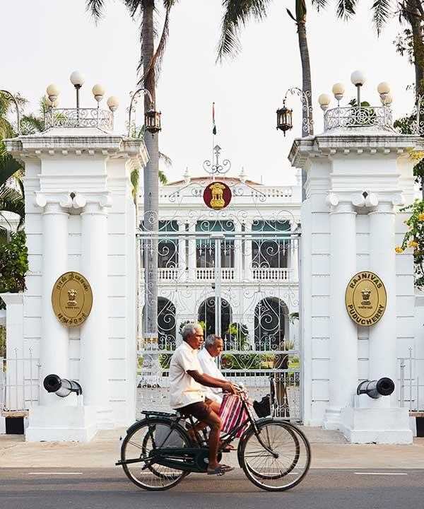 Cyclists pass Raj Nivas, the colonial-era governor's palace, in Pondicherry (Photo: Alicia Taylor)