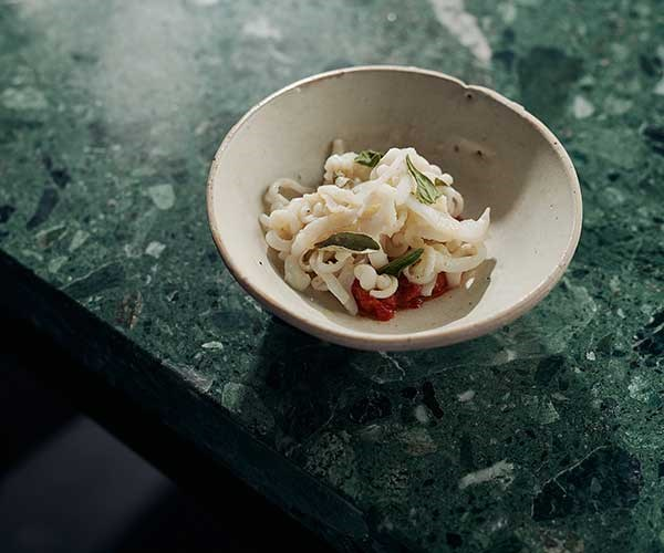 """**Calamari, fermented tomato, 'nduja**  """"We blast freeze and julienne calamari into long strips like pasta, chuck it in a hot pan and then mix it with the fermented tomatoes and [spicy 'nduja](http://www.gourmettraveller.com.au/recipes/explainers/what-is-nduja-2332