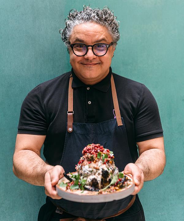 Chef Athanasios Kargatzidis holds Baron's dish of roasted cauliflower with tahini yoghurt and pomegranate
