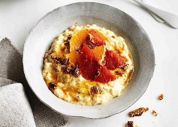 Rice pudding, topped with orange segments and crushed sesame brittle, in a grey bowl, with a grey linen napkin to the left.