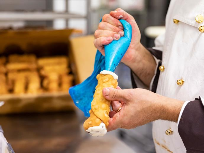 Filling a cannolo.