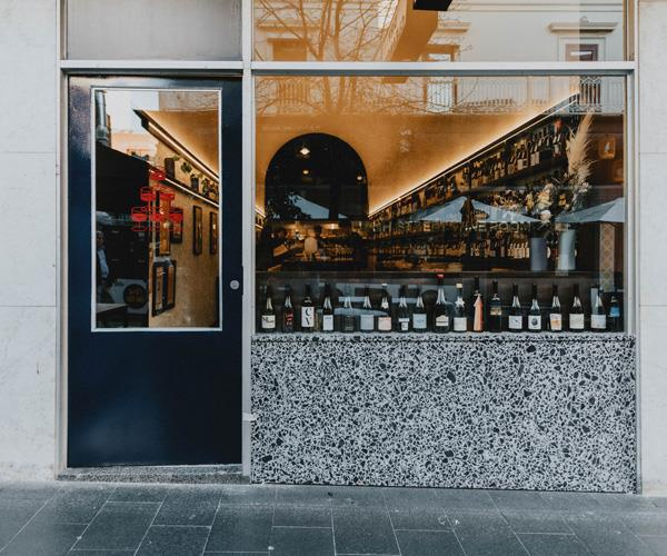 Street view of wine bar Leigh Street WIne Room, with a glass window, lined with wine bottles, looking into a long bar with a curved ceiling, and a navy door open ajar.