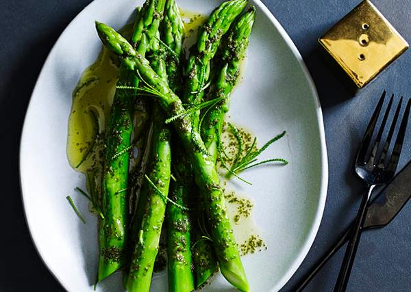 Five asparagus spears drizzled with butter, on a white oval plate, with a golden pepper shaker and black knife and fork on the side.