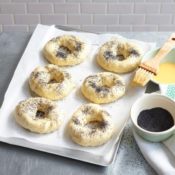 Bagels in the making, brushed with eggwash and scattered with poppy seeds.