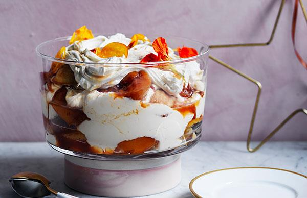 Large, raised glass bowl holding a trifle with peaches, sponge biscuits and cream, decorated with orange flowers.