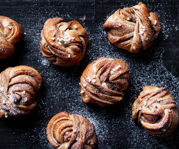 Six twisted buns, dusted with icing sugar, on a black background.