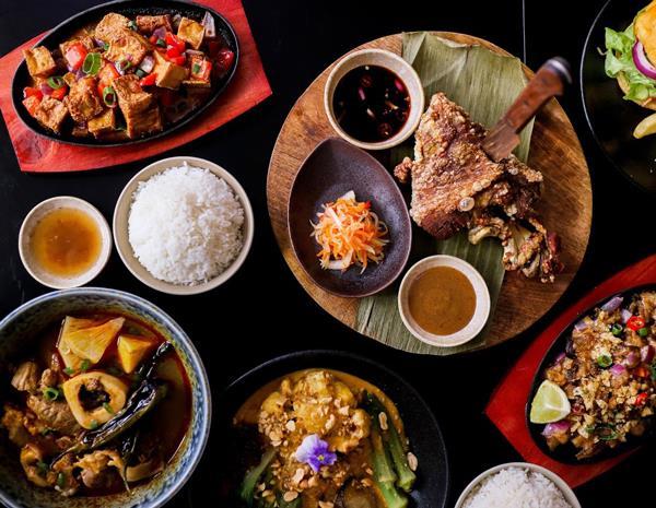 Clockwise, from top left: tofu sisig; crispy pata with atchara, mang tomas, and special dipping sauce; pork sisig; kare-kare; kansi.
