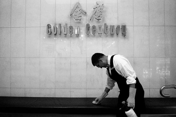A staff member cleans the entrance to seafood restaurant Golden Century.