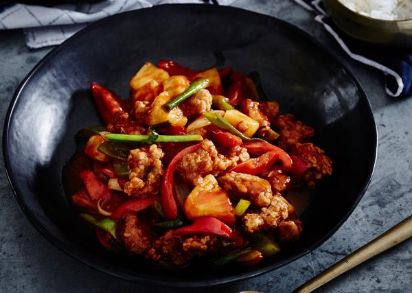 A black bowl holding sweet and sour pork with sliced capsicum and chunks of pineapple
