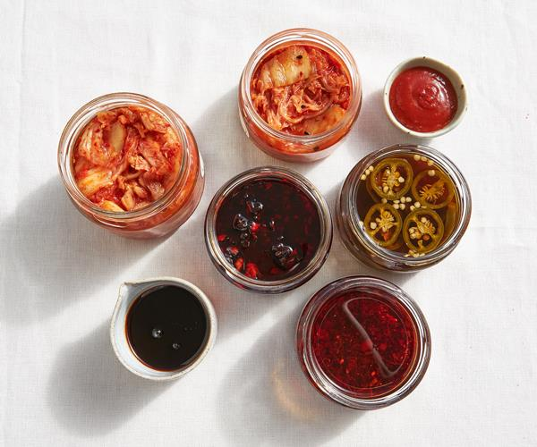 Over the top shot of jars containing kimchi, teriyaki sauce, textural XO sauce, Korean hot sauce and pickled pickled jalapeños o a white surface. The jars cast long shadows on the surface.