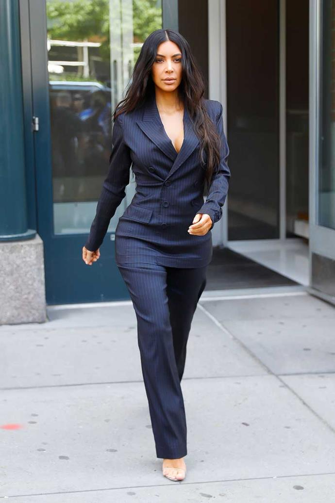 Kim steps out wearing a plunging pinstripe power suit for *Forbes*' Women's Summit in New York City.