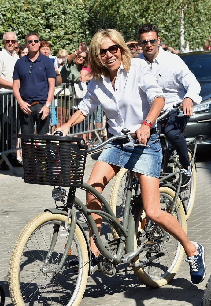 Macron in a white button down, denim skirt and Nike shoes while out with husband Emmanuel Macron on June 17th.